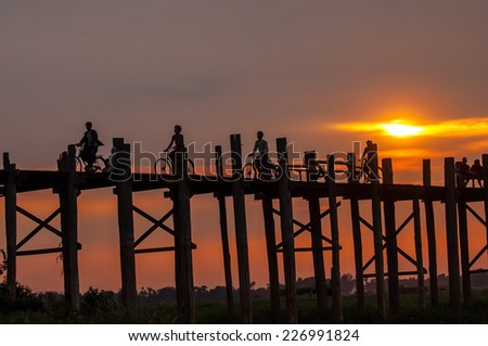 Mandalay,Myanmar-March 16,2011 : Unidentified Myanmar People with bicycle on U-Bein bridge in sunset in Mandalay, Myanmar. The U-Bein bridge is the longest teak bridge in the world, 1.2km lenght.
