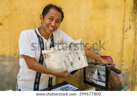 Mandalay, Myanmar - November 18th, 2014: A friendly student offers his paintings to tourists visting his town. - stock photo