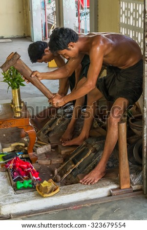MANDALAY, MYANMAR - NOVEMBER 18: Two young craftsman punching gold in the traditional way to make leaf gold. November 18 in Mandalay, Myanmar - stock photo