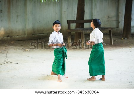 MANDALAY, MYANMAR - NOVEMBER 22: Young Burmese boys with thanaka on their faces in school uniform are playing a top along the road in the town on November 22,2015 at Mandalay, Myanmar.