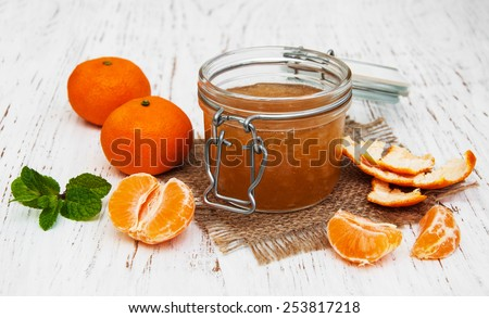 Mandarin jam with fresh fruits on a wooden table - stock photo