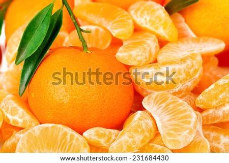 mandarin orange among mandarine slices closeup - stock photo