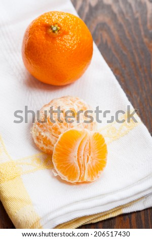 Mandarin orange segments with a whole mandarin in the background on a cloth - stock photo