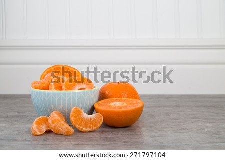 Mandarin orange slices in a blue bowl on a wooden table with unsliced orange nearby - stock photo