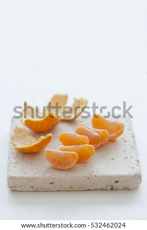 Mandarin orange wedges on natural stone board and white background