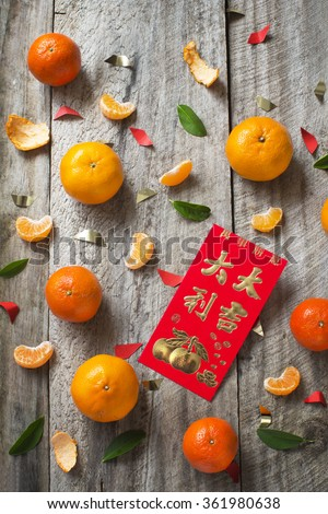 "Mandarin oranges and Chinese new year red packet with text ""Good luck and great fortune"" printed on rustic wooden background. - stock photo"