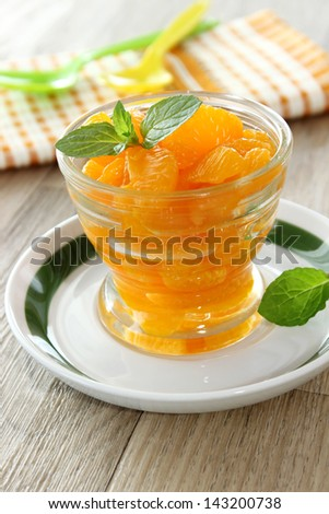 Mandarin oranges from a can in glass and mint leafs - stock photo