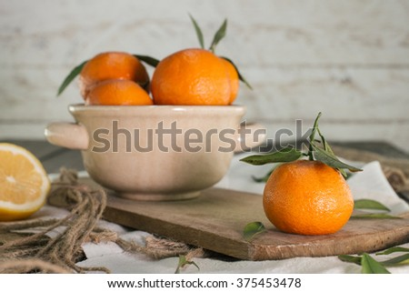 Mandarins and lemon on wooden table - stock photo