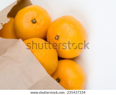 Mandarins clear out of the paper bag closeup isolated - stock photo