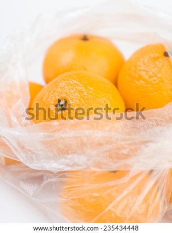 Mandarins in the opened polyethylene bag closeup isolated - stock photo