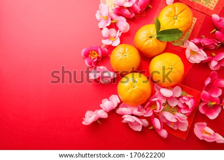 Mandarins with Red Packets and Plum flowers on red background  - stock photo