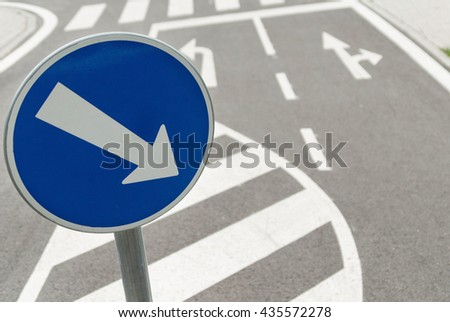 Mandatory direction right turn road sign crossing black asphalt street crossing - stock photo