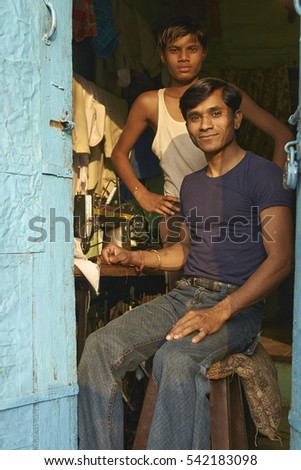 MANDU, MADHYA PRADESH, INDIA - NOVEMBER 19, 2008: Two young men at work in the tailor shop in the rural hilltop town of Mandu in Madhya Pradesh, India.