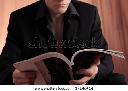 Mane in black suit and shirt holding a magazine