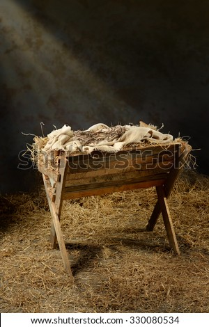 Manger with crown of thorns in barn with light coming from above - stock photo
