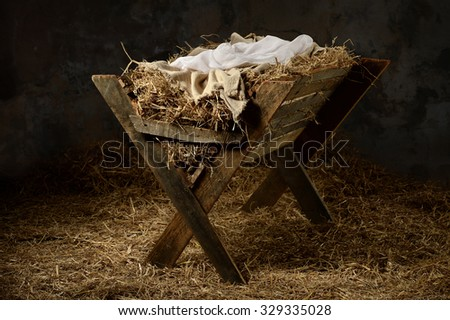 Manger with hay and swaddling clothes in old stable - stock photo