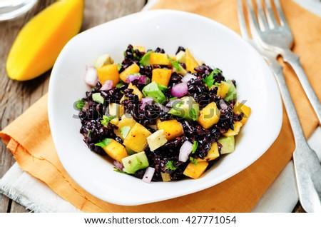 Mango avocado red onion black rice salad. toning. selective focus - stock photo