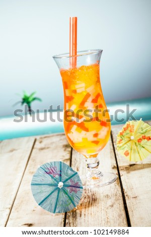 Mango Boba Cocktail Tea standing in front of a beach background with beautiful paper umbrellas. - stock photo