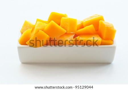 Mango Cubes on a white dish - stock photo