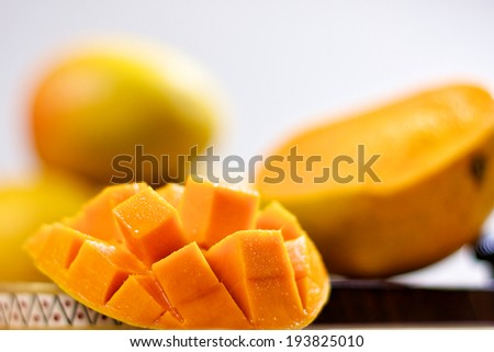 Mango cubes / slices close up / Macro with mangos in background. - stock photo