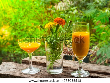 Mango juice in glass on wooden plank
