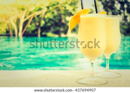 Mango juice with beautiful outdoor swimming pool in hotel resort - Vintage Filter and Sunflare Processing