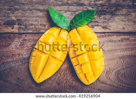 mango on a dark wood background. tinting. selective focus on the mangos slices.vintage tone - stock photo