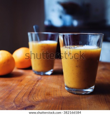 mango orange smoothie with chocolate almond crushed and coconut crated. Dark background and selective focus on glass of orange juice.