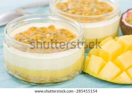 Mango & Passion Fruit Cheesecake - Individual potted dessert made with mango and passion fruit whipped cream and a biscuit base, topped with passion fruit pulp. - stock photo