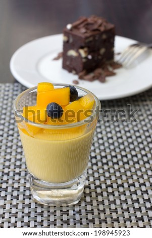 mango pudding in a glass and chocolate brownie as background, canape appetizer