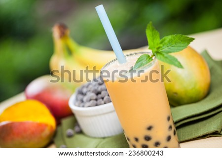 Mango smoothie bubble tea with fruit and tapioca pearls in the garden