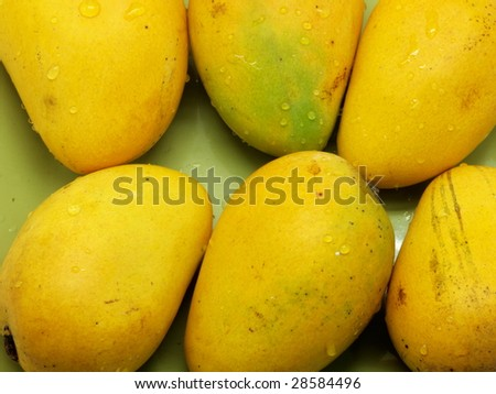 Mangoes on green plate. - stock photo