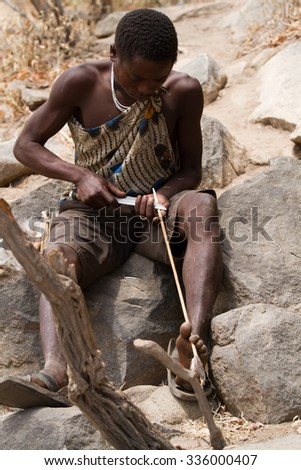 MANGOLA, TANZANIA - AUGUST 14: hadzabe tribesman making an arrow, only about 1000 people of this tribe are left, they still live in the old way August 14, 2015 in Mangola, Tanzania