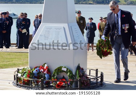 MANGONUI, NEW ZEALAND - APRIL 25 2014:New Zealand Army veteran soldier placing flower wreaths on Mangonui war memorial during Anzac Day War Memorial Service. - stock photo