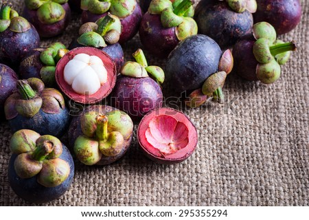 Mangosteen and cross section showing the thick purple skin and white flesh of the queen of friuts, Delicious mangosteen fruit arranged on a hemp sack background, Mangosteen flesh, top view - stock photo