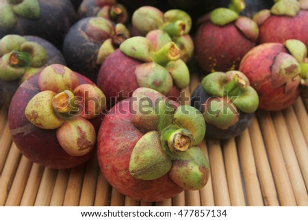 Mangosteen. Closeup of mangosteen showing the thick purple skin and white flesh of the queen of friuts, Delicious mangosteen fruit arranged on wooden background, Mangosteen flesh, closeup.