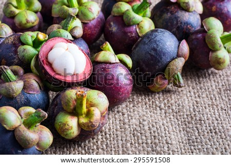 Mangosteen flesh and cross section showing the thick purple skin and white flesh of the queen of friuts, Delicious mangosteen fruit arranged on a hemp sack background. - stock photo