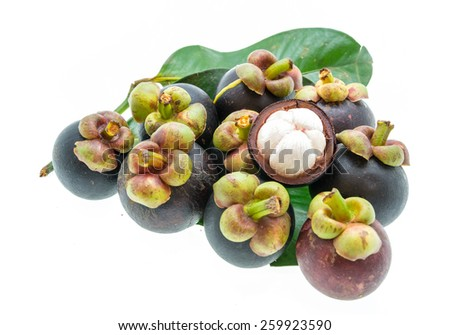 Mangosteen fruit and cross section showing the thick purple skin and white flesh of the queen of fruits. - stock photo