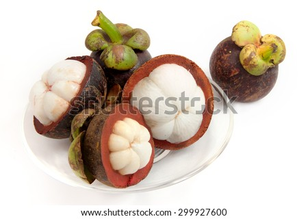 mangosteen fruit split on a clear glass plate on isolated white with clipping path a tropical fruit with sweet juicy white segments of flesh inside a thick reddish-brown rind.
