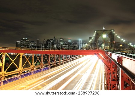 Manhattan and the Brooklyn Bridge in New York by night - stock photo