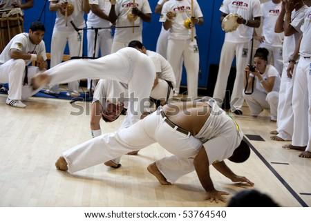 "MANHATTAN BEACH, CA - SEPTEMBER 13: Mestres (masters) spar or ""play"" in the roda (circle) at the 11th annual International Capoeira Festival in Manhattan Beach, CA on Sept. 13, 2009. - stock photo"