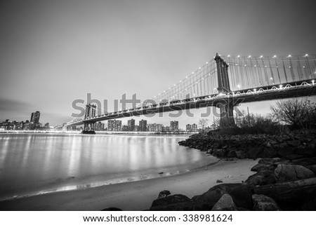 Manhattan bridge and New York City downtown skyline at dusk with skyscrapers illuminated over East River panorama. Copy space. Black and white image. - stock photo