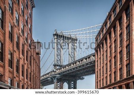 Manhattan bridge seen from narrow buildings on a sunny day