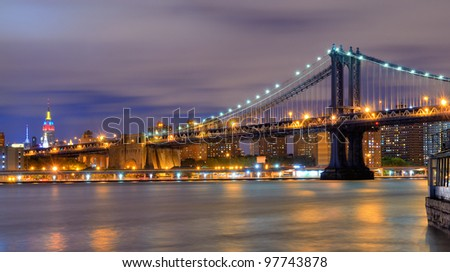 Manhattan Bridge Spanning the East River towards Manhattan and the Empire State Building. - stock photo