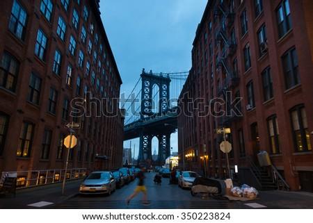 Manhattan Bridgeas at dusk as seen from Washington street in Brooklyn, New York City, USA.  Motion blured jogger running in foreground.  - stock photo