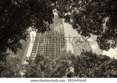 Manhattan buildings framed by Central Park trees. - stock photo