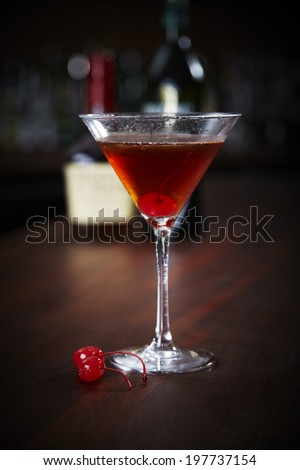Manhattan cocktail in a martini glass with cherries - stock photo