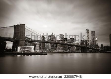 Manhattan Downtown urban view with Brooklyn bridge at night - stock photo