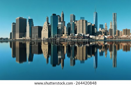 Manhattan financial district with skyscrapers over East River with reflection. - stock photo