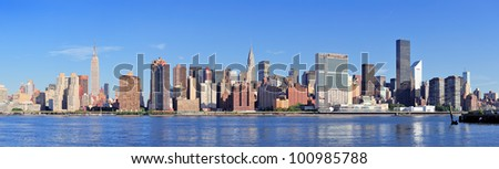 Manhattan midtown skyline panorama over East River with urban skyscrapers and blue sky in New York City - stock photo